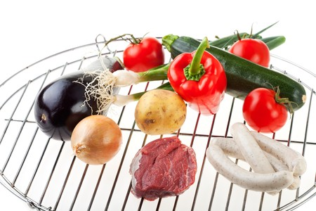 raw meat, sausages and vegetables on a gridiron photo