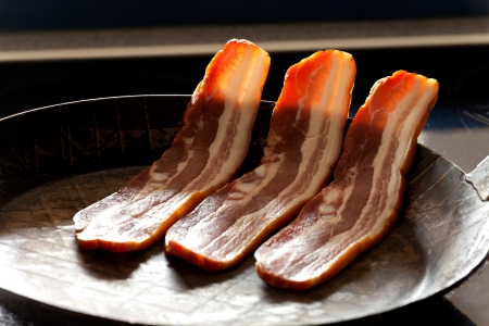 three stripes of bacon in a pan