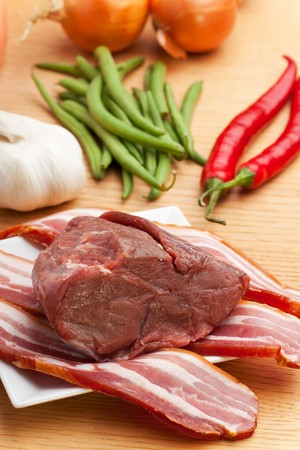 raw meat and bacon stripes on a wooden table Stock Photo - 7667545