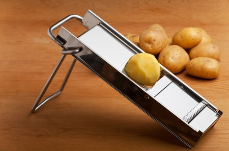 SLICER: half a potato on a mandolin slicer Stock Photo