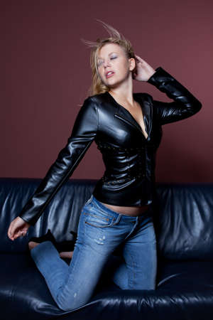 woman in a leather jacket on a couch photo