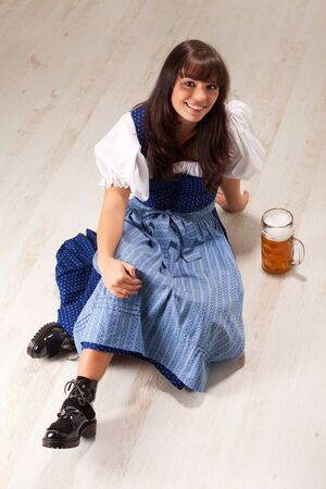 sitting bavarian girl in a costume with a beer mug Stock Photo - 8133210