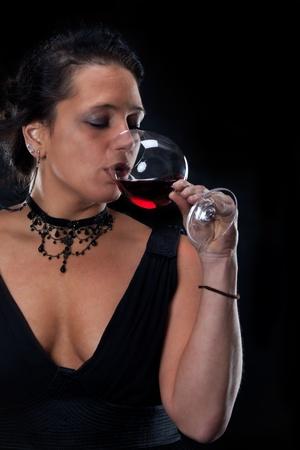 beatiful lady in an elegant dress drinking red wine