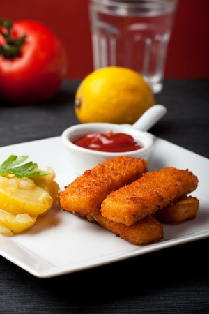 closeup of fish fingers with potato salad