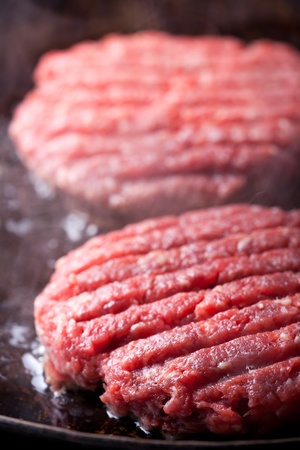 two beef patties in an iron pan Stock Photo - 8819024