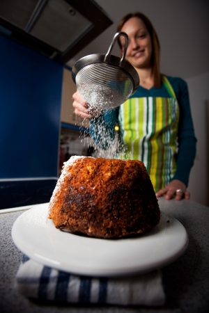 young cheffe dusting sugar on a cake Stockfoto