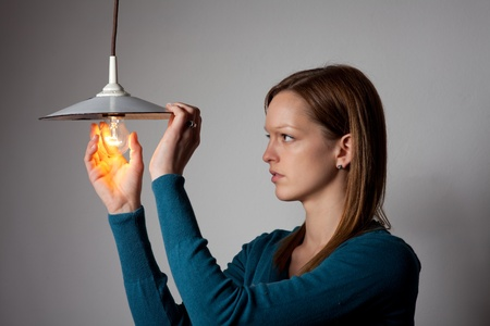 young woman changing a light bulb