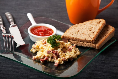 scambled eggs with ham cubes on a glass plate photo