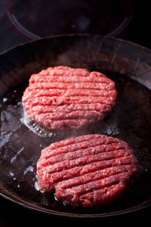 minced beef: two beef patties in an iron pan Stock Photo