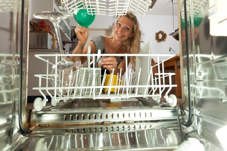 young woman seen from inside of a dish washer Stock Photo