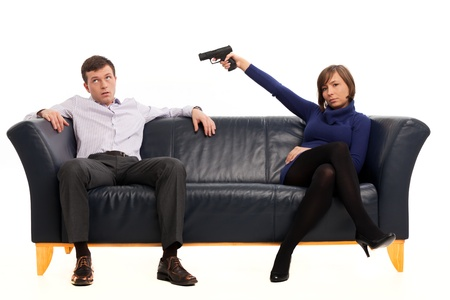 women with guns: isolated couple on a couch with a gun