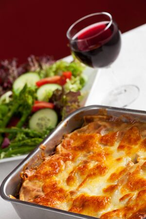baking dish with lasagna and salad photo