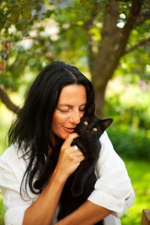 dark haired woman with a cat outdoor photo