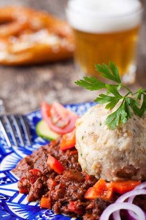 goulash with dumpling on a blue plate photo