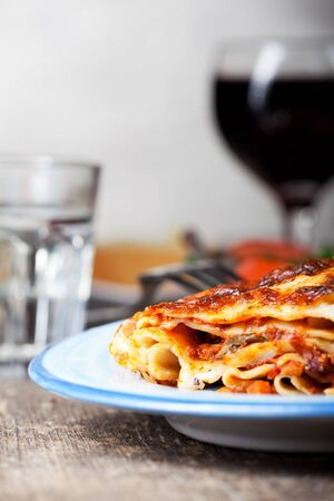 browned: fresh lasagna dish on a blue plate