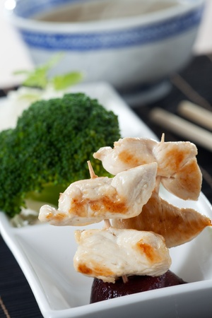 grilled chicken meat on a skewer with chop sticks  photo