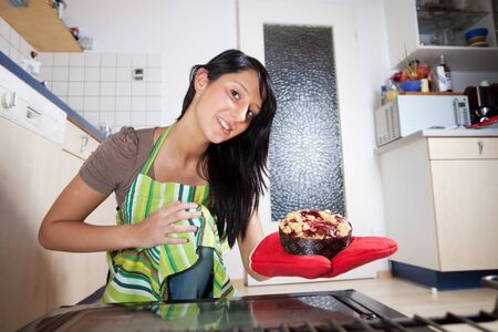 gorgeous woman with a cake seen from inside of a stove Stock Photo - 16327537