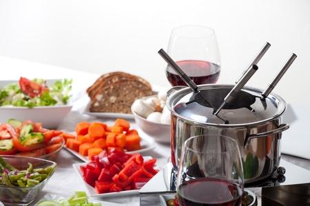 Tisch mit Fondue-Set und Zutaten Standard-Bild - 11762528