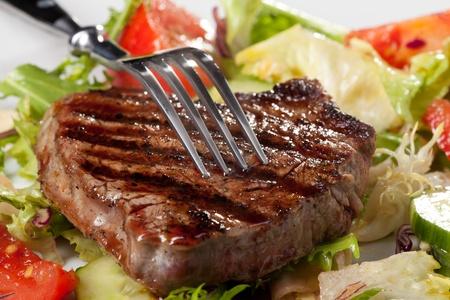 closeup of fork on a grilled steak  Standard-Bild
