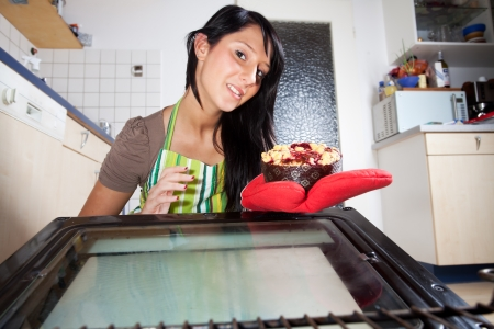 woman fetching a cake from an oven  Stock Photo - 16335363