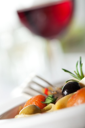 closeup of pasta with tomatoes and olive