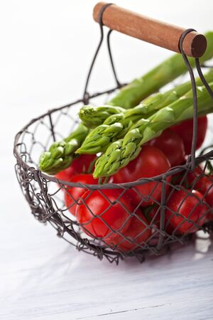 wire basket with tomatoes and asparagus Stock Photo - 14478200
