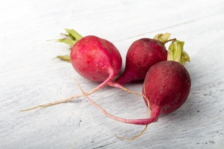 three radishes on wood  photo