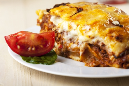 lasagna on a plate with tomato slice