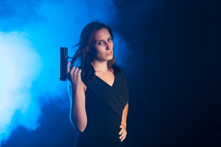 woman with a gun in the fog Stock Photo - 16335385