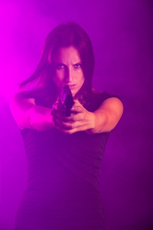 woman with a gun in the fog Stock Photo - 16335386