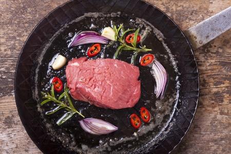 steak cru: steak cru dans une po�le de fer