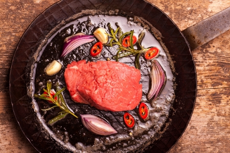 raw steak in an iron pan  Stock Photo - 19087104
