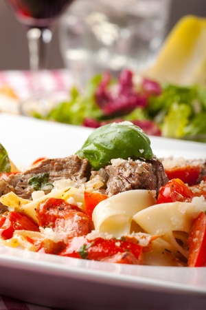 Tagliatelle with steak and tomato  photo