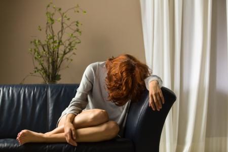 mujer llorando: Mujer en un sofá