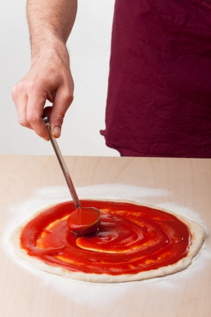 pouring tomato sauce on a pizza  Stock Photo - 19385151