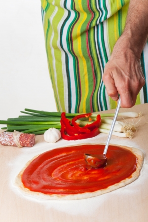 pouring tomato sauce on a pizza  Stock Photo - 19385162