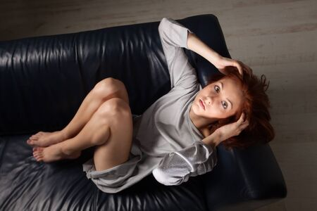 beatiful redhead on a sofa  Stock Photo - 20951633