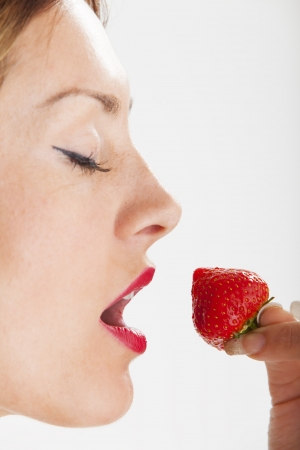woman eating a strawberry  photo