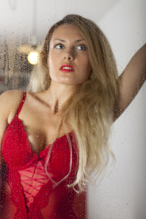 woman in lingerie seen through a window  photo