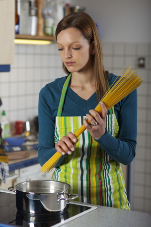 woman cooking pasta in a kitchen  photo