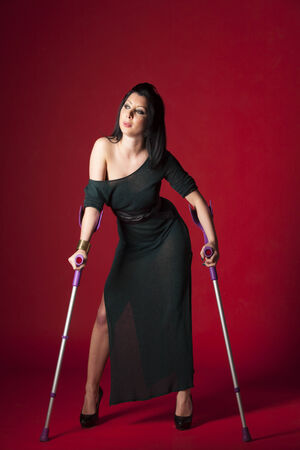 crutch: woman in a green evening gown with crutches  Stock Photo