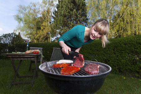 grill tongs sausage: woman and a barbecue