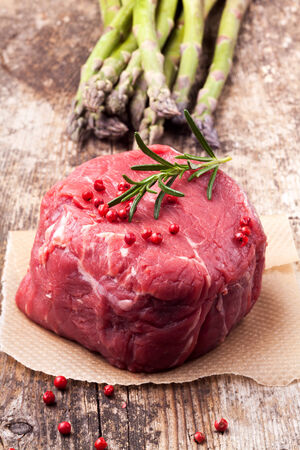 raw steak with asparagus on wood photo
