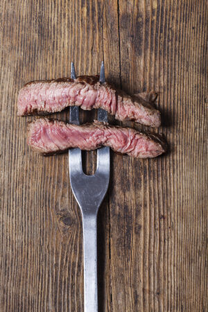 slices of a steak on a meat fork photo