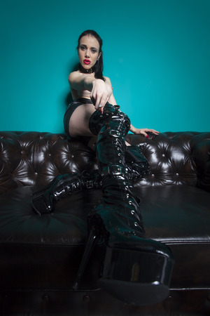 masochism: dominatrix in leather on a couch