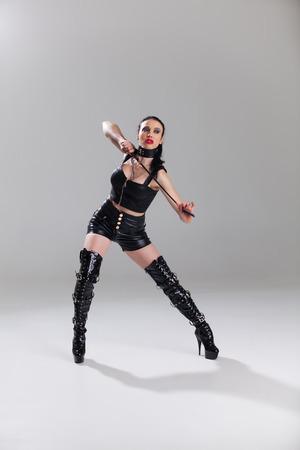 Domina in Leder mit einer Peitsche