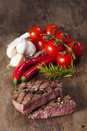 slices of a steak on a wooden plank photo