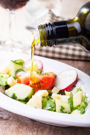 food dressing: pouring olive oil over salad Stock Photo