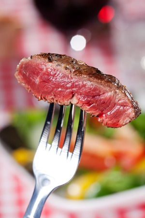 slice of a steak on a fork over salad Stock Photo