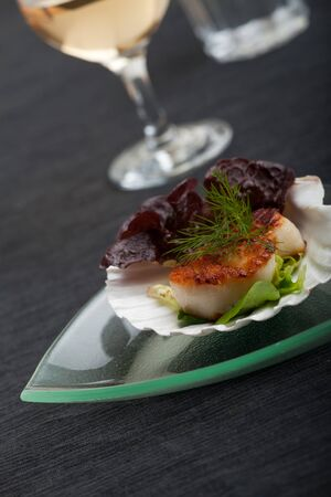 placemat: grilled scallops in their shell on a black placemat